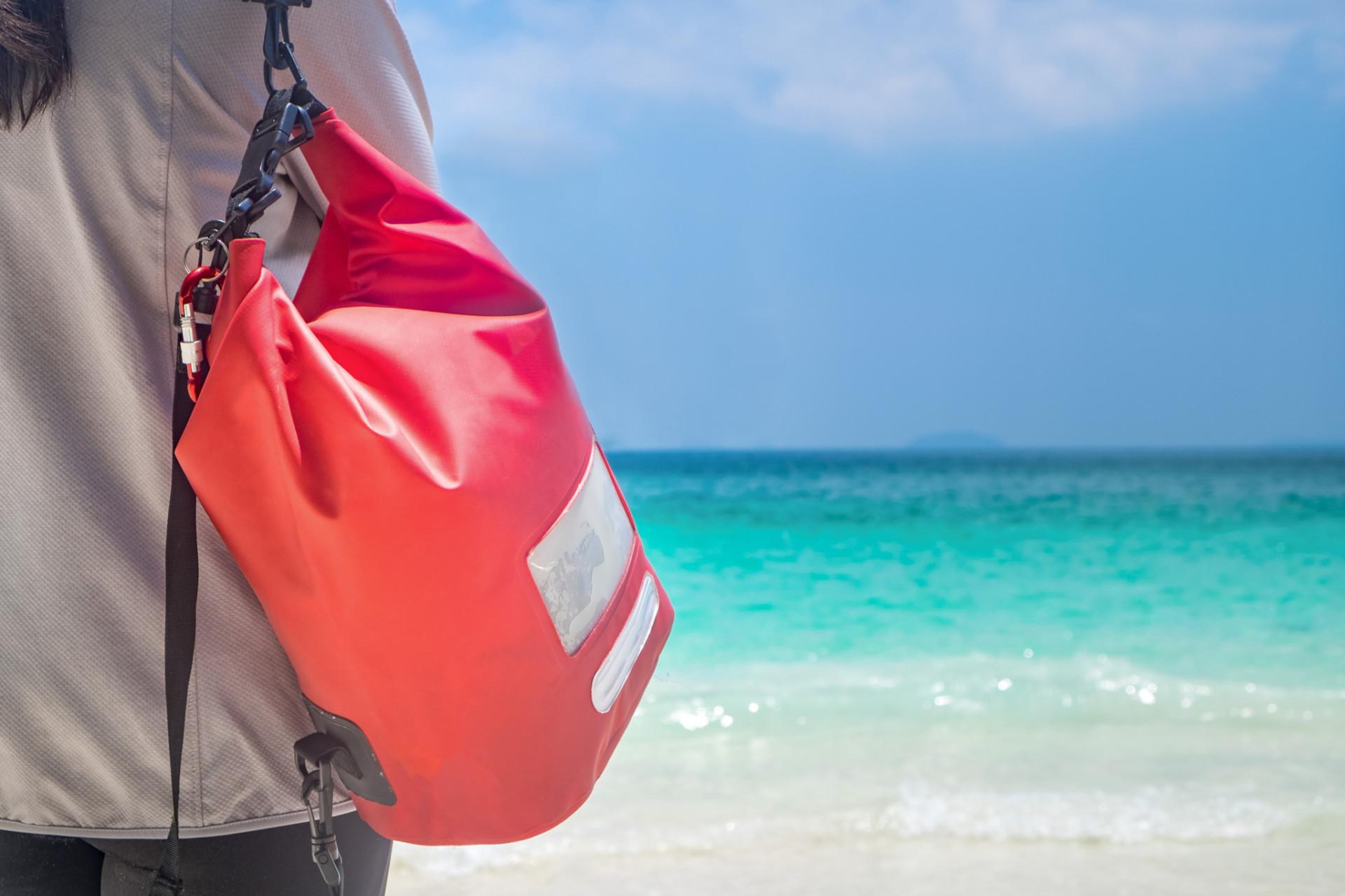 Frau mit Dry Bag am Strand